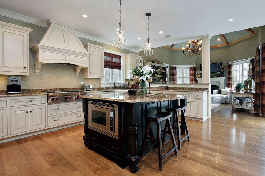 Within this sprawling, open-plan kitchen, the island stands in sharp contrast, flaunting a black stained wood construction and beige granite countertop. The island houses a stainless steel microwave, in addition to a curved expanse of countertop that provides ample dining space for a pair of wood bar stools.