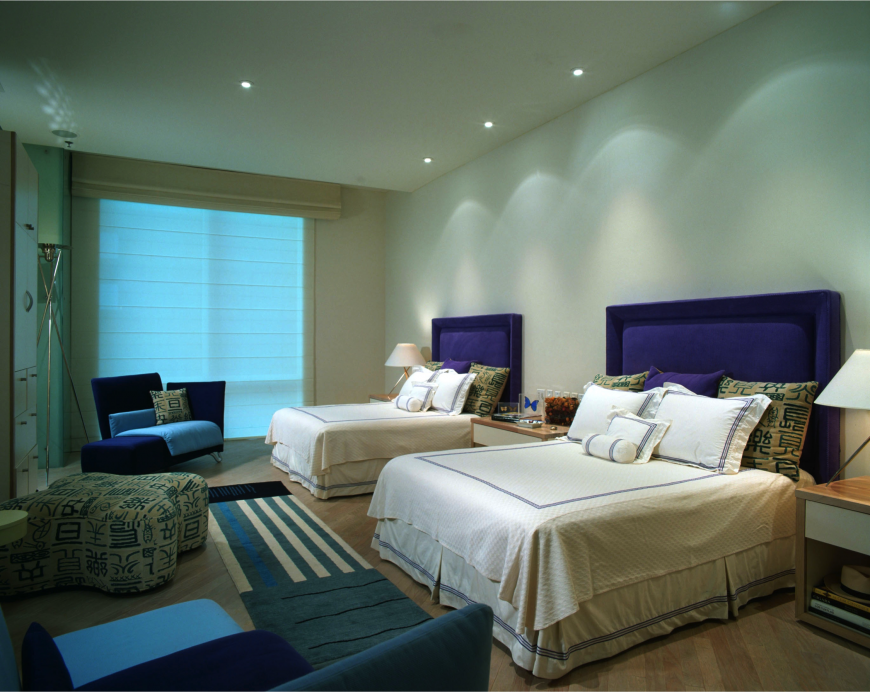 This beautiful bedroom is full of great colors and patterns. The fabric headboards here are a bold royal purple.
