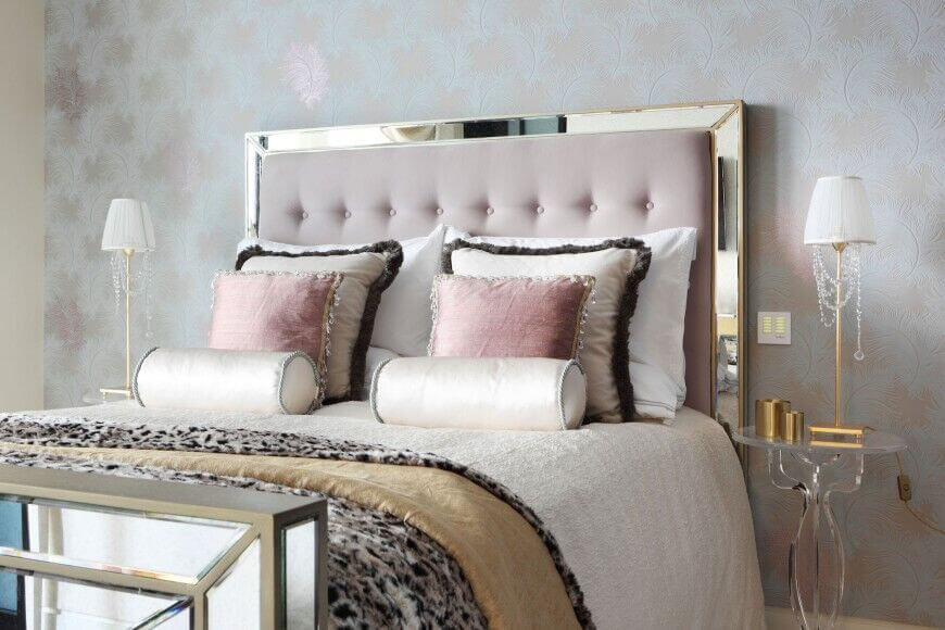 This bedroom is very elegant and beautiful. The soft pinks in the headboard and pillows create a great accent against the glass bed frame and white sheets.