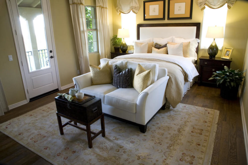 This bedroom has a bright canary yellow feel to it. The headboard contrasts the yellows and dark hardwood with a cream colored fabric