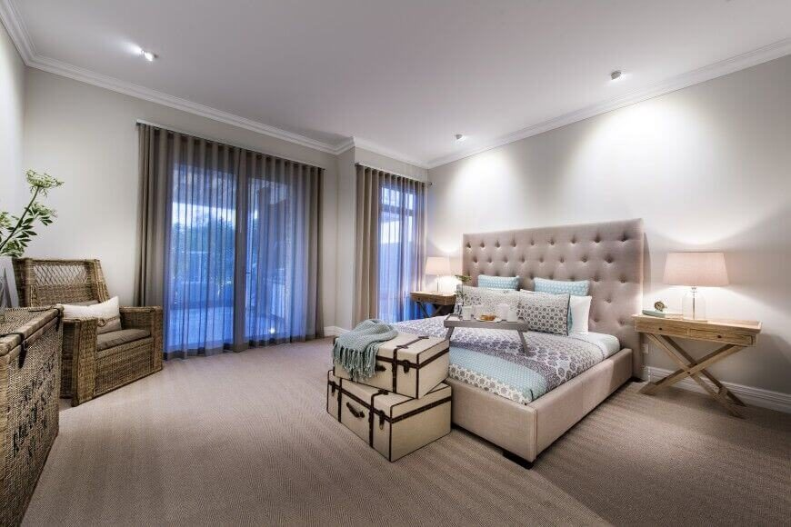 This bed has an oversized button tufted headboard with a neutral color scheme. The entire bedroom is elegant with mostly neutral color hues.