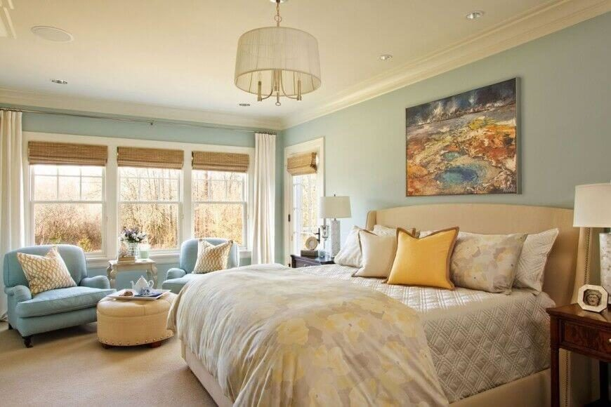 This beautiful country styled bedroom has a subtle upholstered headboard. Soft touches of blue and yellow add a tranquil atmosphere to this space.