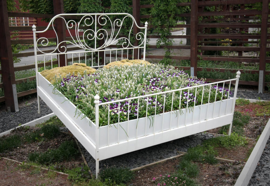 This repurposed bed frame makes for a lovely, large planter in this garden.