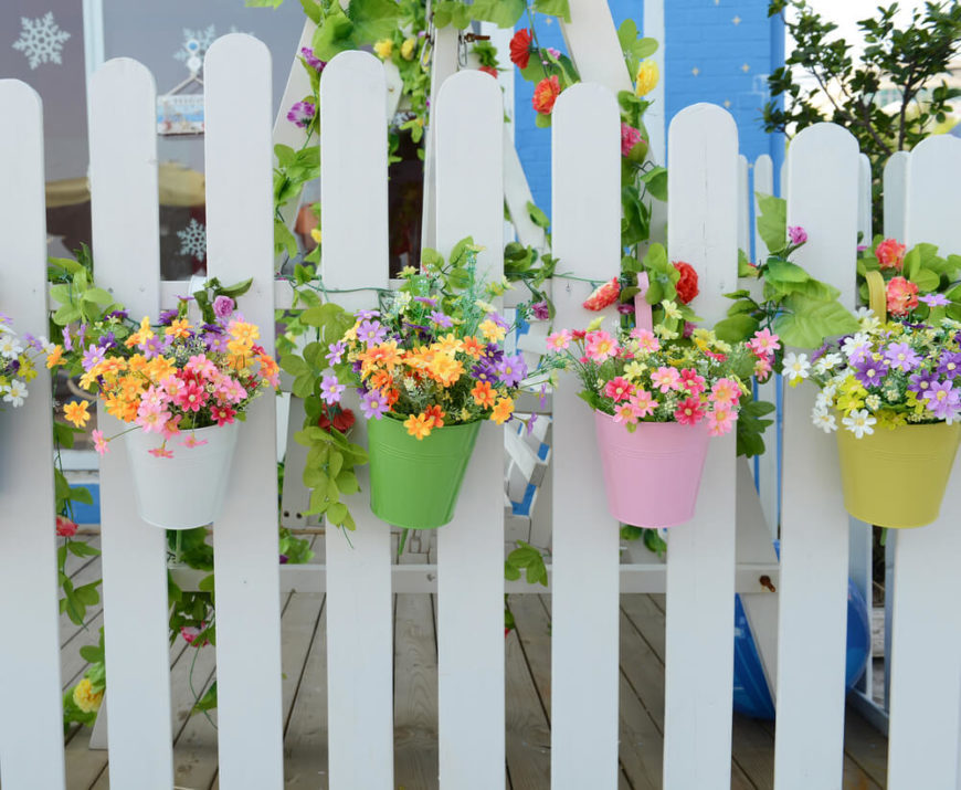 These cute little pastel buckets bring whimsical charm to this white picket fence. Coordinating and contrasting colors pull the whole display together.
