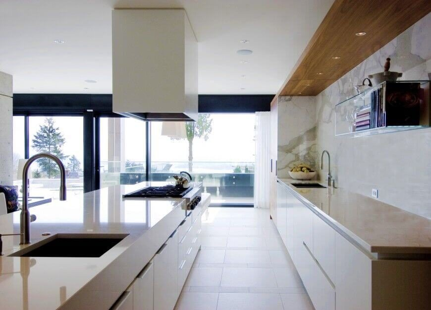 This Sleekly Modern Kitchen Appears Brightly Lit Via Wraparound Glazing,  With Light Hued Tile Flooring