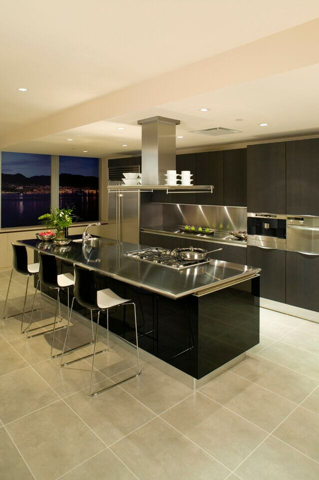 In an ultra-modern kitchen boasting stainless steel countertops and large format tile flooring, the lengthy island in black features a large gas range and full sink built-in. Dark stained minimalist cabinetry completes the picture.