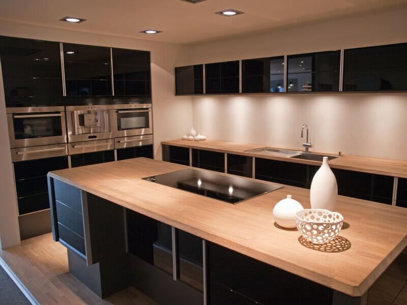 This sleek, high contrast modern kitchen features glossy black cabinetry juxtaposed against light natural wood countertops and flooring. The large island boasts a glass-flat range, matching the black hue of the cupboards.