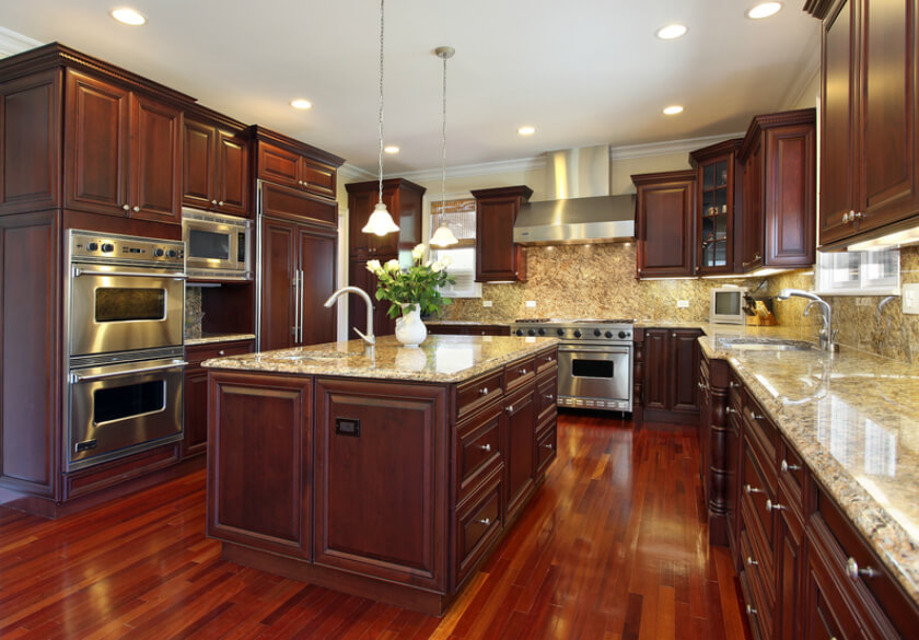This ultra-luxurious kitchen flaunts rich cherry wood from floor to ceiling, with ornate cabinetry all around. Beige granite countertops add a splash of contrast and brightness, which continues on the island surface. With a built-in sink and array of storage drawers, the island is a highly functional center of this kitchen.