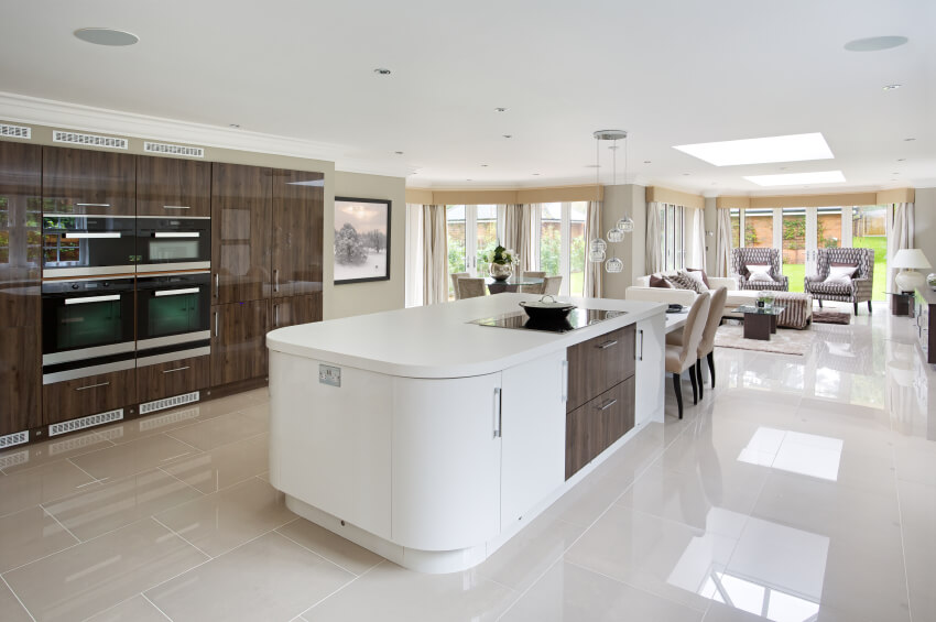 In an ultra-modern home with a wide open-plan design, the kitchen is clearly defined by the immense, curved white island at center. Boasting a high contrast section of natural wood cabinetry, matching the surrounding floor to ceiling cupboards, the island houses a smooth surface range and a dining table extension.