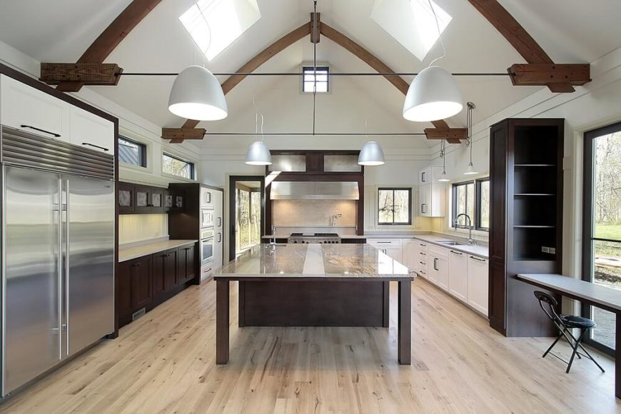 This bright kitchen stands below a massive vaulted ceiling with exposed natural wood beams, centered on a massive island with a full size dining table extension. The glass surface shows off the rich wood construction, which contrasts with the lighter hardwood flooring and white cabinetry throughout the kitchen.