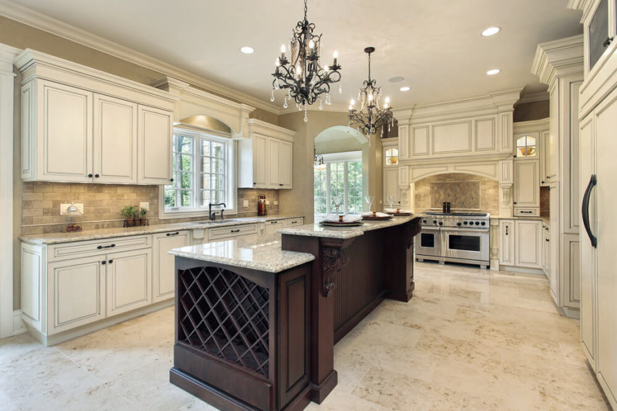 Now we come to another luxuriously appointed kitchen, bright and bold with white cabinetry and light marble flooring. The wide expanse is punctuated by the rich, dark wood two-tiered island, housing a large wine rack and plenty of in-kitchen dining space on the granite countertop.
