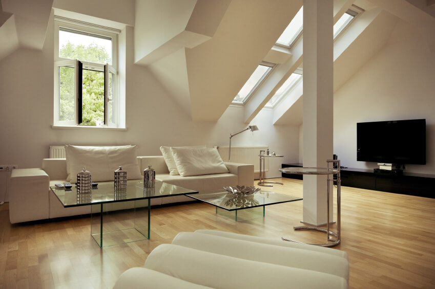 A Mellow Living Room With Light Wood Floors And Ample Sunlight. Glass  Coffee Tables Allow