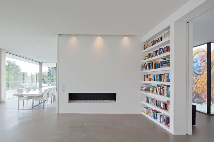 Simple built-ins continue the clean design while books add color and a point of interest in the upper floor living room. The street art and water-atrium of the foyer can be seen in the background.