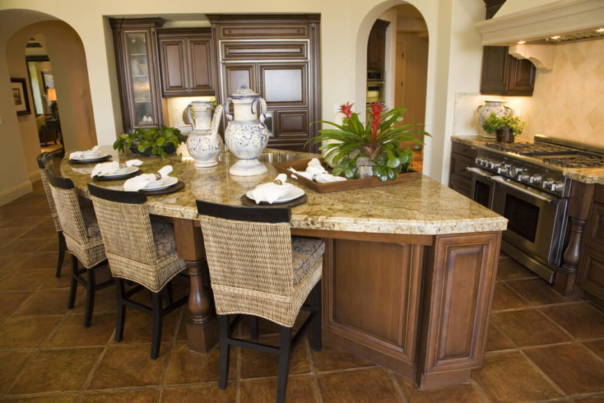 This novel design is a broad, angular kitchen island with a large swath of dining space and built-in sink on the beige granite countertop. Rich natural wood construction matches the surrounding cabinetry, meshing well with the brown tile flooring.