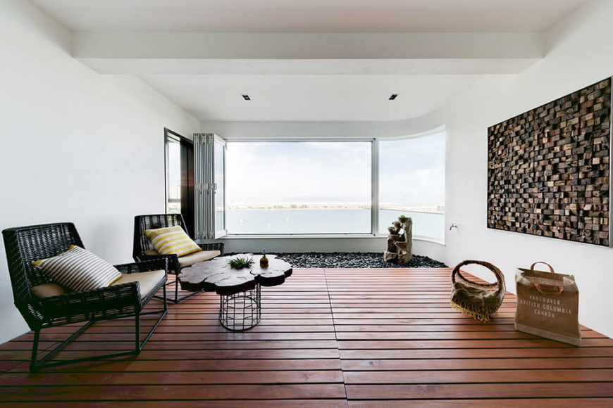 Off the living room is an extended balcony featuring wooden paneled floors and a small rock garden overlooking stunning views of the ocean beyond. The art on the wall was created using small, unevenly textured cubes of wood to add dimension to the white walls.