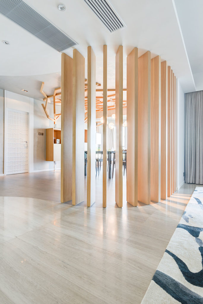 The dining room and living room are divided by 13 oak veneered fins, curved to match the floor design. This offers privacy while also allowing ventilation to flow uninhibited through the two rooms.