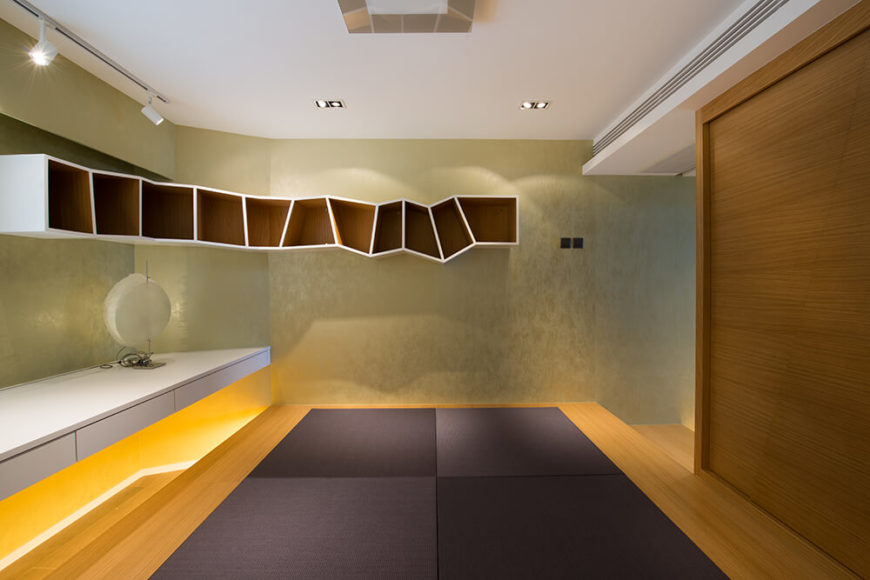 A short corridor away from the dining and living rooms is a multi-purpose room in brighter shades. It has a raised tatami-styled floor and a built in desk that runs the length of one wall. The bookshelf's unusual angles add to the playfulness of the room.