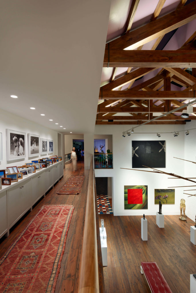 A catwalk hallway spans the length of the gallery, flanked by natural wood railing and a lengthy set of cabinetry topped with family portraits.