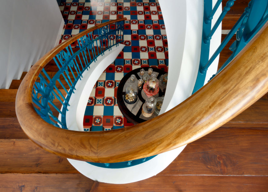 The spiraling staircase curves toward the highly detailed floor patterns with rich hardwood construction and blue painted metal. It's a rare element of curvature in this angular home.
