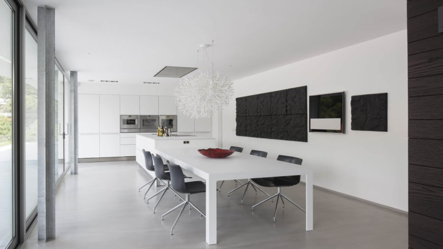 The dining room and kitchen are in an open floor plan together. The black and white colors of the room, along with the abstract center piece above the table, make this space a contemporary masterpiece.