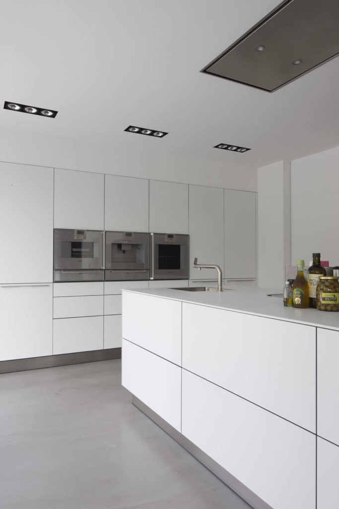 The kitchen has a lot of hidden storage spaces that are disguised within the unique linear pattern in the walls. The appliances are built directly into the wall for a spacious room.