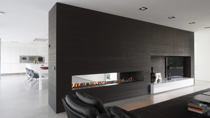 The living room and dining room are separated by a large wall, made of dark natural wood. A serene fireplace can be seen on both sides resides within the wall.