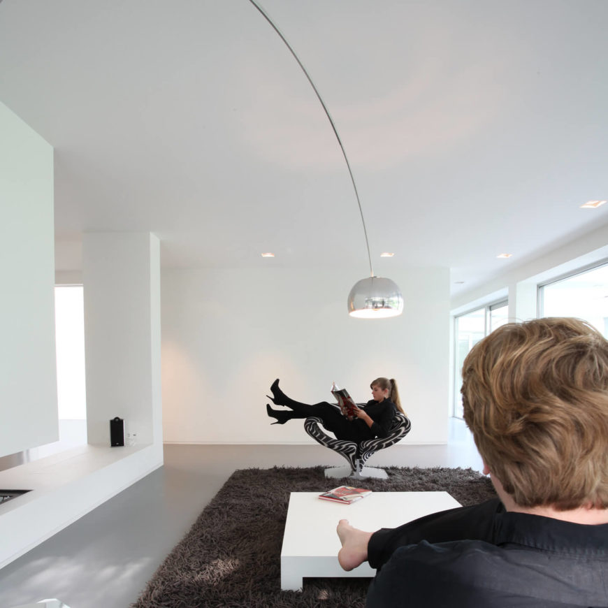 The living room is a brilliant white color with large windows lining the wall for lots of natural illumination. A large dark colored rug and swirled black and white chair add contrast to this beautiful room.