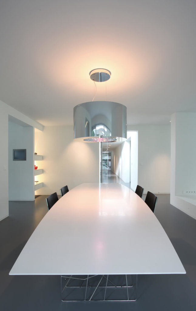 A large curved table sits in the center of a communal area. A cylinder shaped metallic light adds a beautiful amber haze to this simple room.