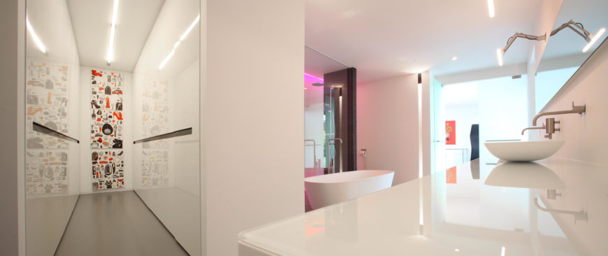 An angled view of the master bathroom showcasing the color-changing neon lights in the shower area and a glass top counter with vessel sinks.
