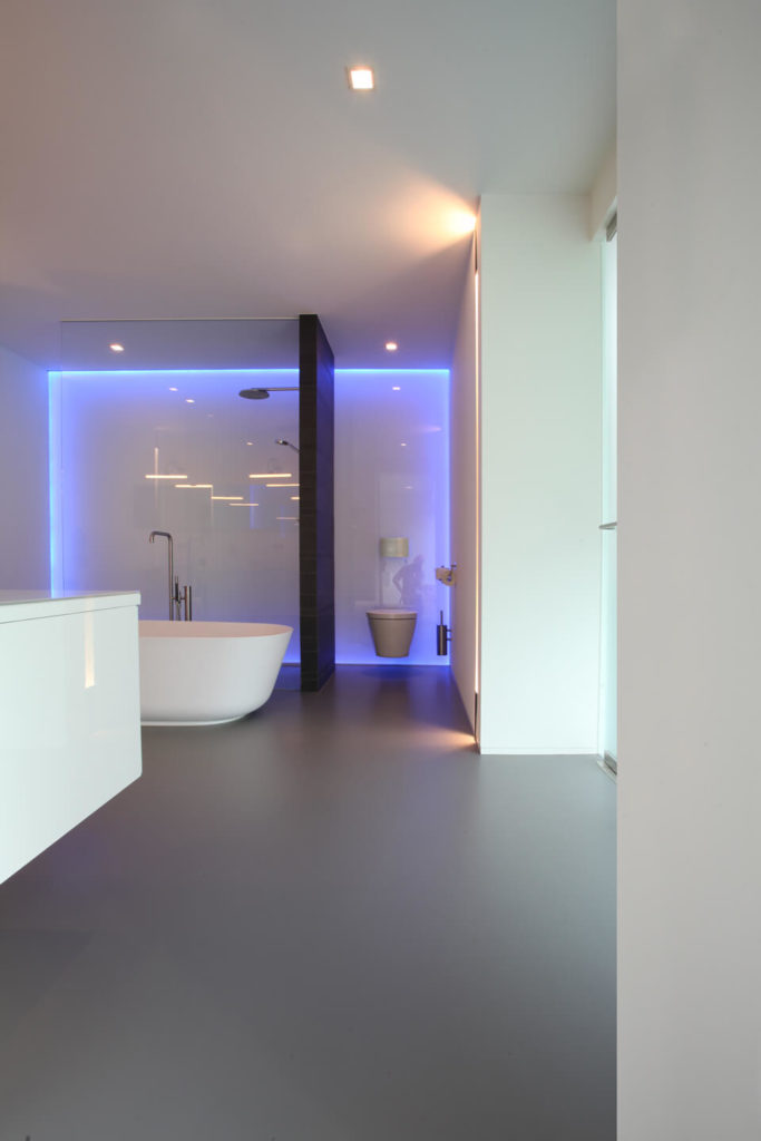 Gorgeous master bathroom features a walk-in shower and toilet area accented with neon lights and divided by a dark wood plank wall.