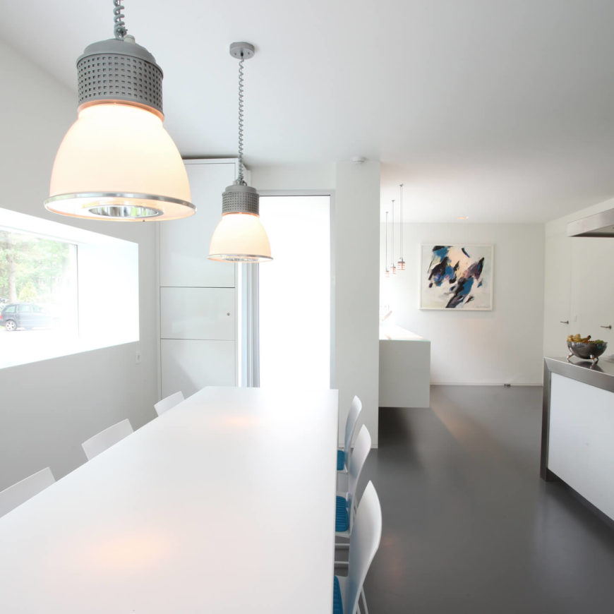 The dining room and kitchen have an open floor plan and natural light filtering through large picture windows. The chairs have blue seat cushions to provide a splash of color against the white room.