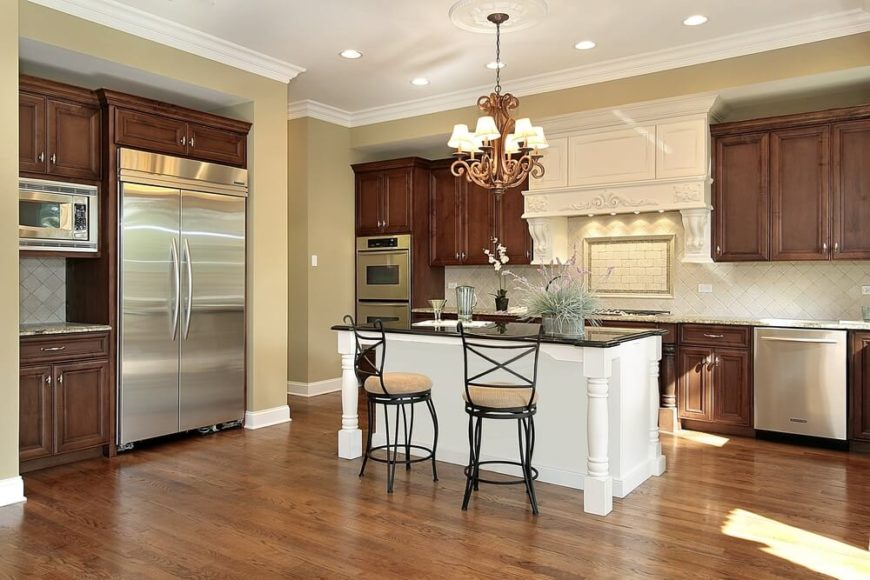 In an open but traditionally appointed kitchen wrapped in natural wood cabinetry, the elegant white island at center draws attention while subtly reflecting the white tile backsplash. In contrast with the hardwood flooring and beige granite countertops, a black countertop on the island truly punctuates the scene.