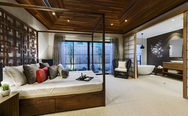 The wooden tray ceiling provides height to this Asian-inspired master suite. Shoji doors can close off the lovely zen master bathroom on suite. The lovely slim wooden four poster bed has an ornate headboard and storage