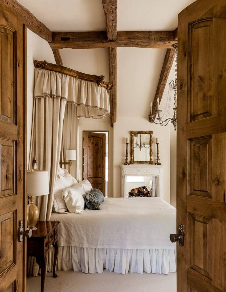 Rustic double doors provide entrance to this lovely traditional master bedroom with a touch of rustic charm. A passthrough fireplace is shared with the master bathroom beyond. A half-canopy rises above the headboard, adding further elegance with thick cream drapes.
