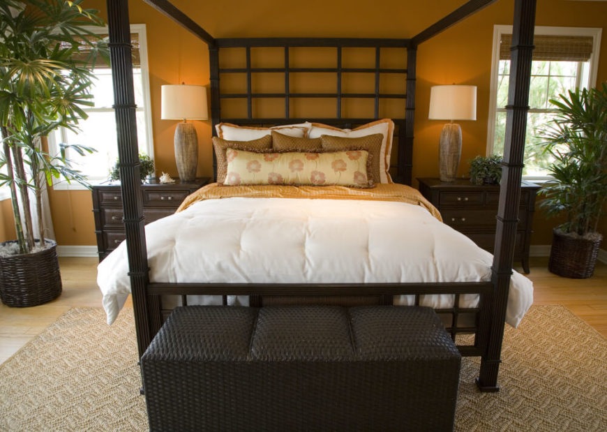 Beautiful bedroom with dark wood furniture and a four poster bed.
