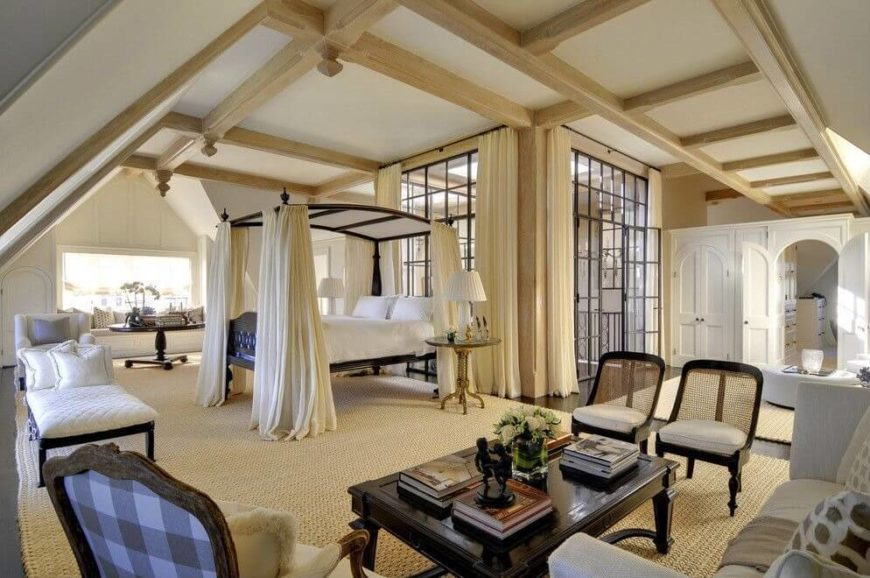 The sheer enormity of this master suite is awe-inspiring. Exposed beams throughout add an architectural detail that is difficult to ignore. A large glass enclosure in the center of the room leads to the stairs.