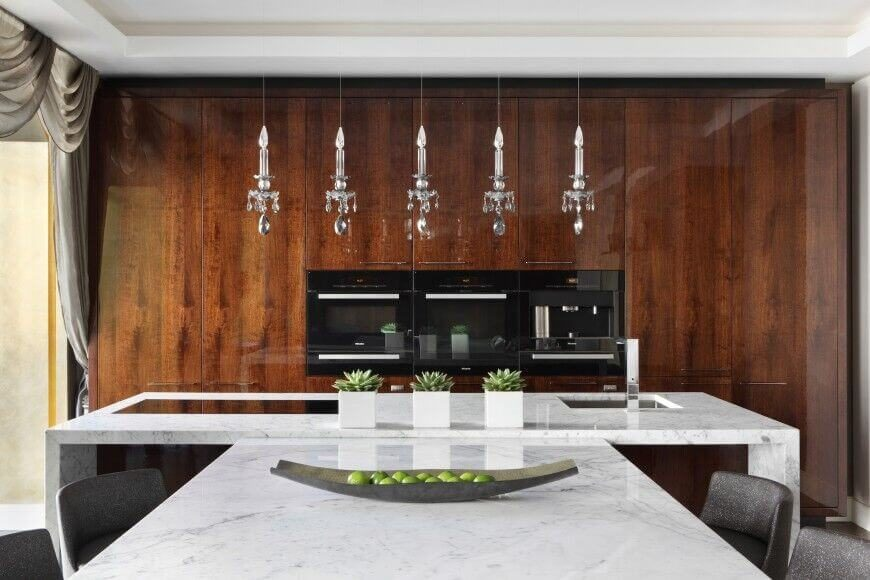Here, slim appliances are nestled into a glossy wall of rich wood cabinets. A dining table in white marble extends directly from the island, and five crystal single candle lights hang above the island.