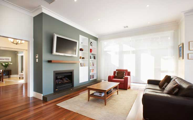 The dark hardwood flooring contrasts with the lighter hardwood in the smaller living area. This family room features a third fireplace, leading one to believe that relaxation, warmth, and comfort were among the family's goals when enlisting LSA for design services. More built in shelving, and simple and modern furniture make this room comfortable and stylish. The bright red accent chair takes center stage and ties in with the same bold colors seen throughout the home. Large veiled windows allow natural light to filter in.