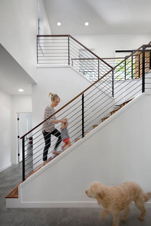 On the more private end of the home, we see a two-flight staircase in rich natural wood, adding a warm contrast to the white and grey surroundings.