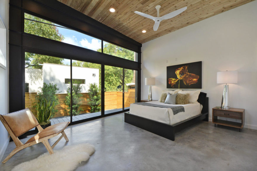 Master bedroom features a vaulted wooden shiplap ceiling with a mounted white fan. It has a light wooden chair accented with a faux fur rug over concrete flooring.