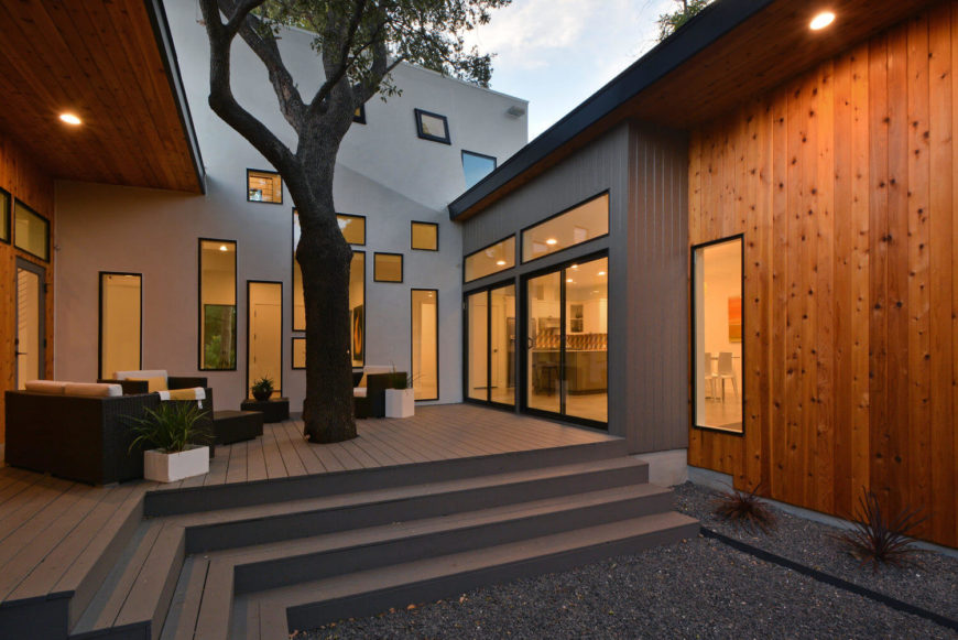 The contrast between expanses of grey, natural wood, and white create a shuffling palette surrounding the courtyard. Ample windows extend the visual presence both indoors and out.