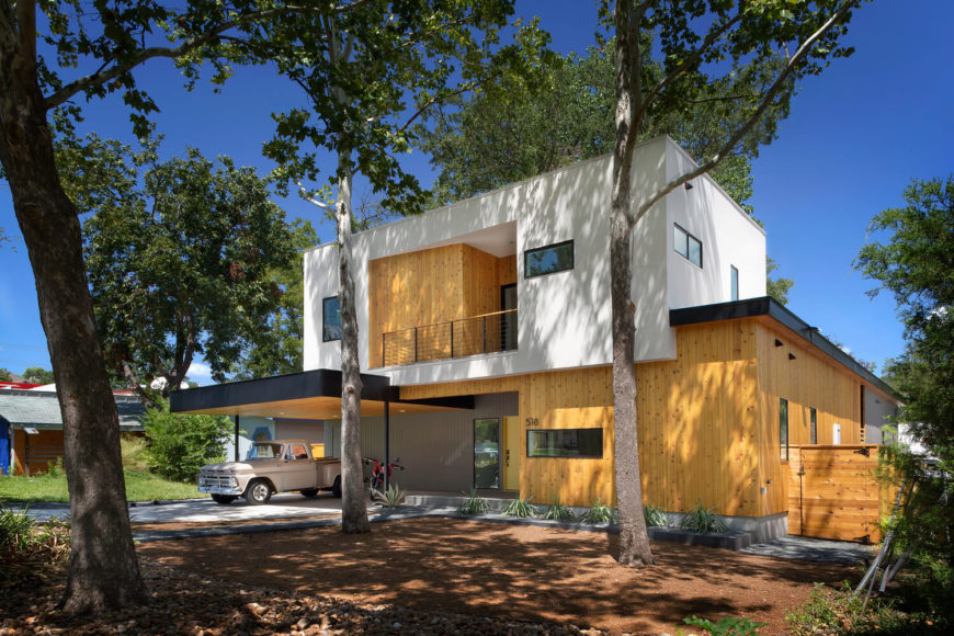 The public face of the home features a floating white upper level over rich natural hardwood paneling.