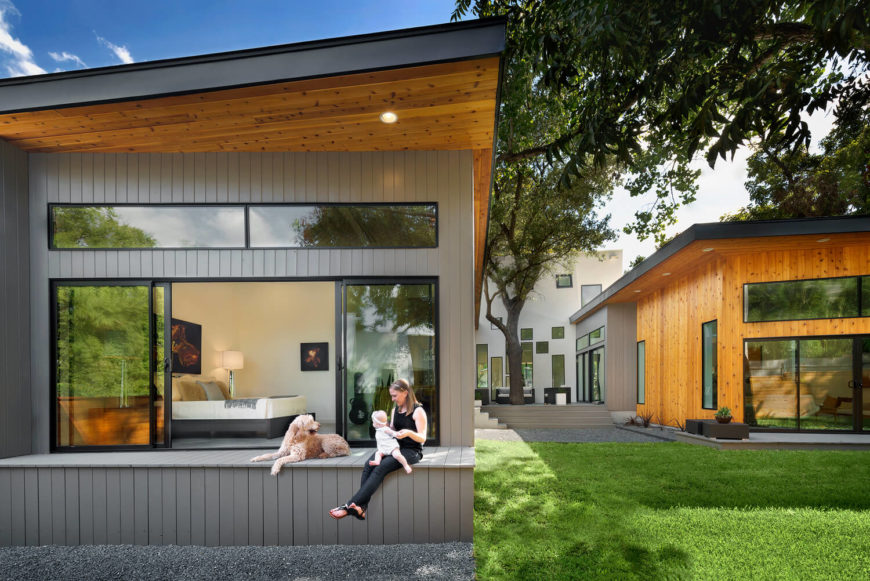 Seen from the back, the pair of single floor wings reach outward from the two story hub, hugging a cozy courtyard space. The bedrooms and other spaces all feature expansive windows, affording expansive landscape views.