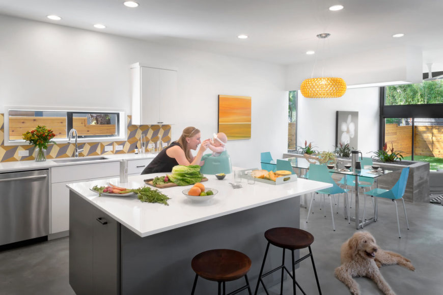 The kitchen centers on a large island with sleek white countertops. Bursts of color within this room appear via the patterned backsplash, dining chairs, and pouring in through the vast windows.