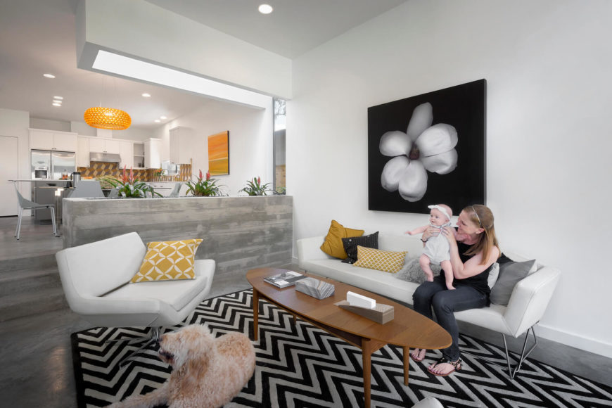 Divided by a concrete indoor planter, mounted below a specially placed skylight, the living room sees contemporary leather sofa and chair paired with a light wood coffee table over a zebra rug.