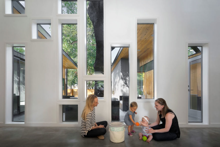 Returning to the central transitional space, we see the asymmetrical array of windows revealing the expansive courtyard, in perfect contrast to the neutral white and grey interior.