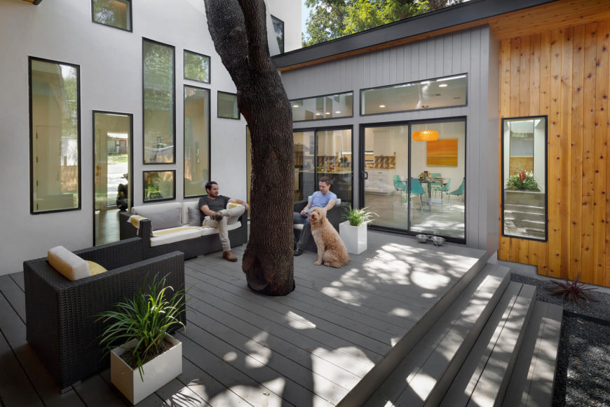Here we see the preserved oak at the center of the property, wrapped in light grey patio decking and surrounded by various sized windows. A set of rattan deck furniture allows for nature centric gatherings.