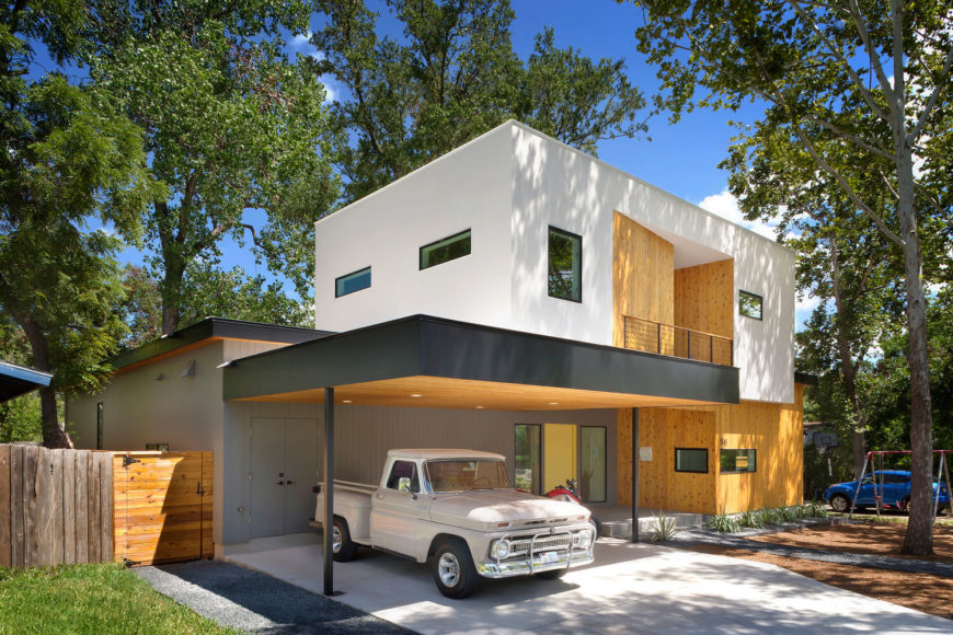 The standout white box design, floating over natural wood paneling, makes for an imposing presence when seen from the street. A lengthy overhang protects a parking space, encompassing the grand entry as well.
