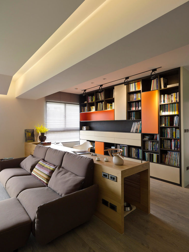 The desk design clearly delineates the home office from the living room. Here we see a closer view of the immense wall-size bookshelf, spiked with bursts of orange paneling.