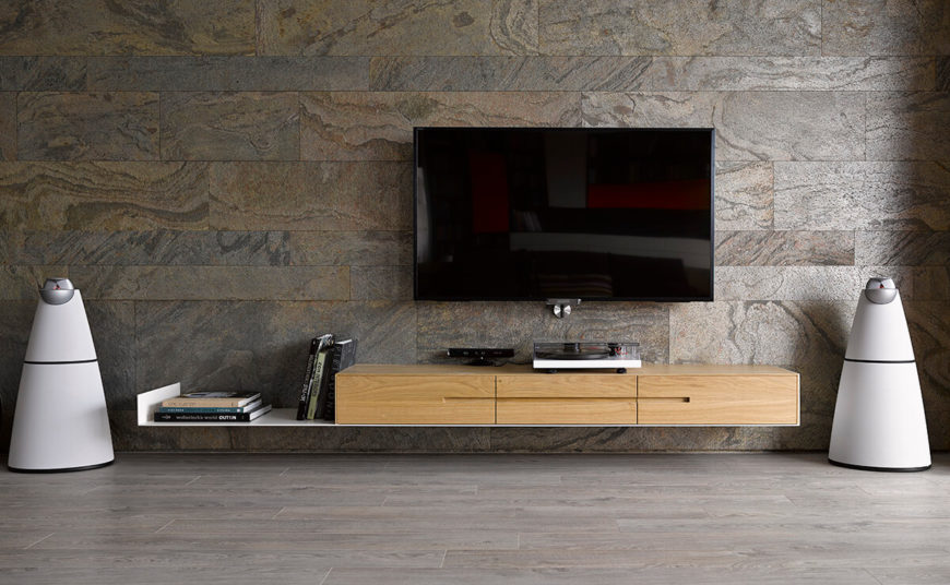 The stone wall houses the audio-visual equipment, including the pair of ultra-modern, conical floor speakers in white. These flank the floating media shelf in natural wood, a seamless expression of the design philosophy of this home.